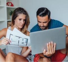 Couple looking at computer and floorplans
