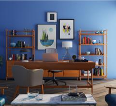Living room space with blue wall, framed wall art, herringbone flooring and wooden shelving