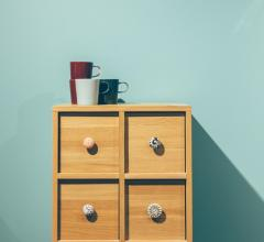Dresser with four coffee cups on top in front of a teal wall