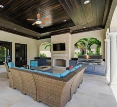 Outdoor kitchen and dining space with fireplace designed by Tres Jolie Maison