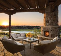 Patio with furniture and fireplace overlooking golf course at sunset