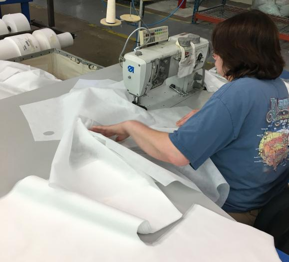 HSM employee sewing medical gowns