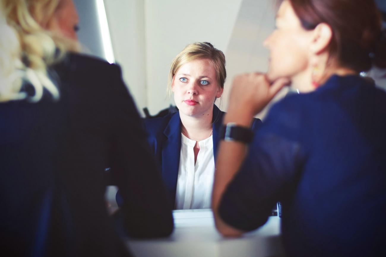 Stock photo of two women interviewing a third woman
