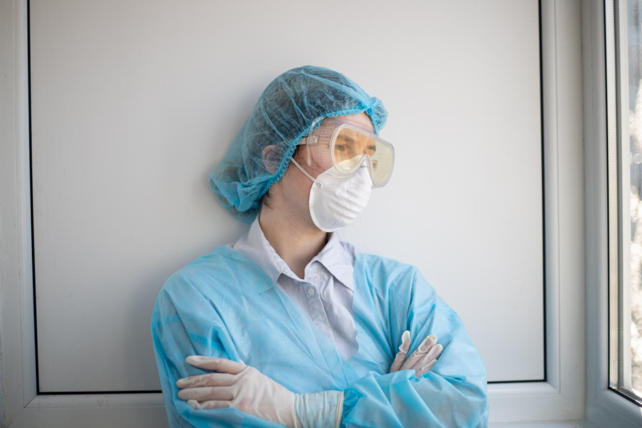 woman in blue scrub suit and mask