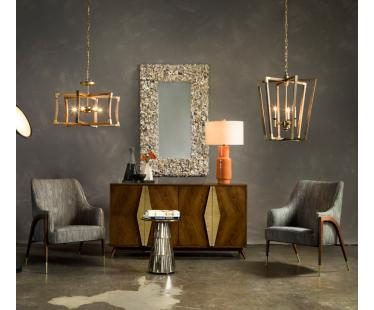 A vignette of products from Currey and Company, including two chairs, one buffet, two chandeliers and a table lamp with an orange base